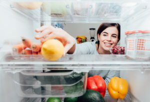 smiling woman reaching into a refrigerator for a lemon